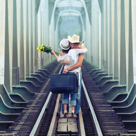 Young couple hugging on a train tracks photo