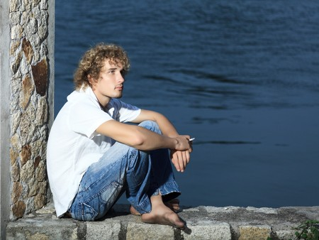 Young man sitting near the river at twilight time photo