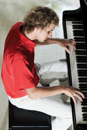 Handsome young man playing on the piano photo