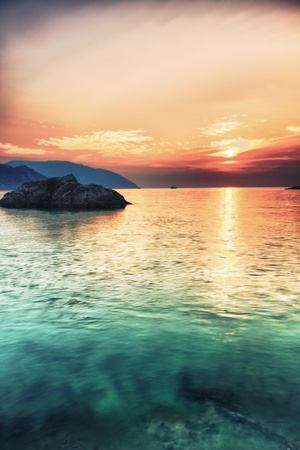 Sunrise over the sea. Stone on the foreground Stock Photo - 8736317