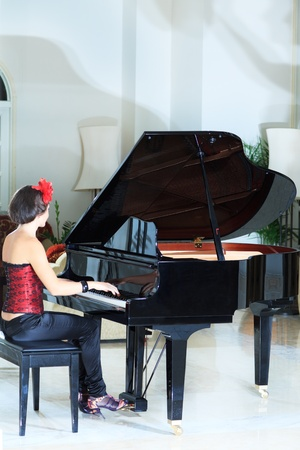 Attractive young woman playing on the piano photo