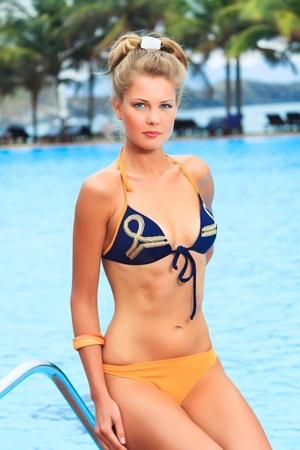 Beautiful woman in bikini near swimming pool  photo