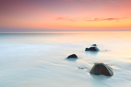 con dao: Sunrise over the sea. Stone on the foreground