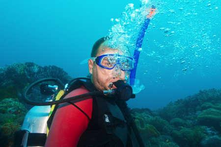 Scuba diver underwater making bubbles photo