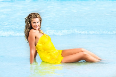 Beautiful woman in yellow dress on the beach photo