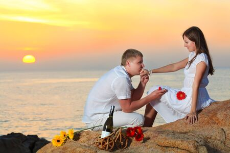 Man proposing to girlfriend and offering engagement ring 免版税图像