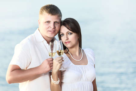 Young couple with glasses of champagne near the ocean  Stock Photo - 9366021