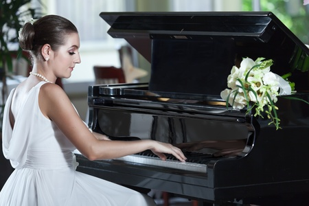 Young beautiful bride playing the grand piano photo