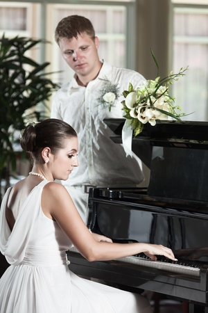 Bride playing grand piano for her groom photo