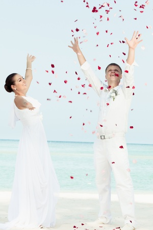 Bbride and groom throwing petals on the  beach photo