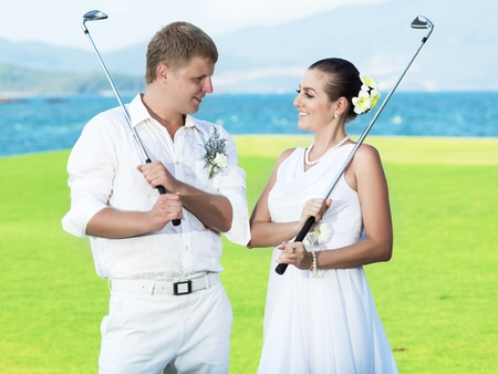 Bride and groom are playing golf at wedding day photo