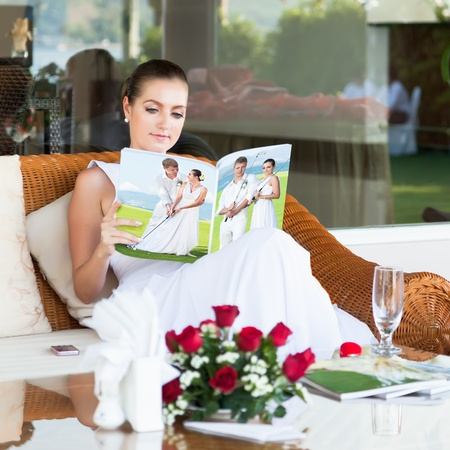 Beautiful bride sitting and reading magazine about golf