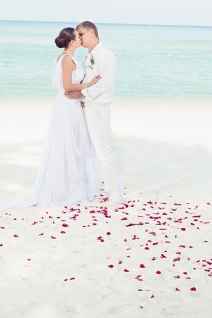 boda en la playa: Bbride y novio bes�ndose en la playa tropical