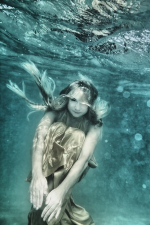 Young beautiful woman in golden dress underwater photo