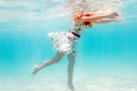 Young beautiful woman in white dress underwater