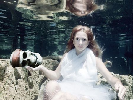 Woman with skull in white dress underwater photo