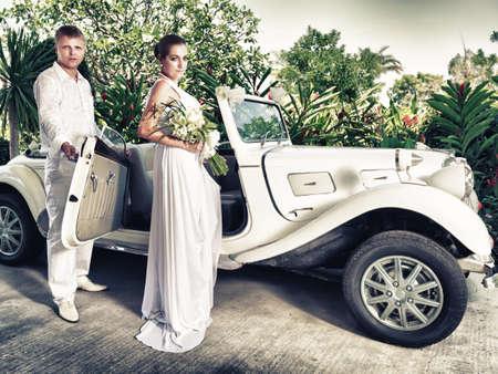 Bride and groom near the retro car photo
