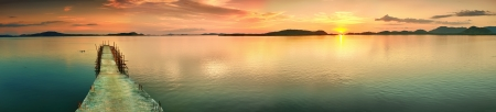 panorama view: Sunset over the sea. Pier on the foreground. Panorama