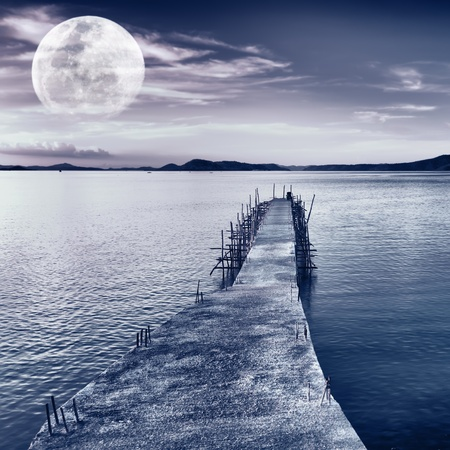 moonlit: Pier on the sea at night time. Moon in the sky