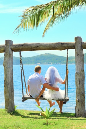 nude bride: Rear view bride and groom on the swing