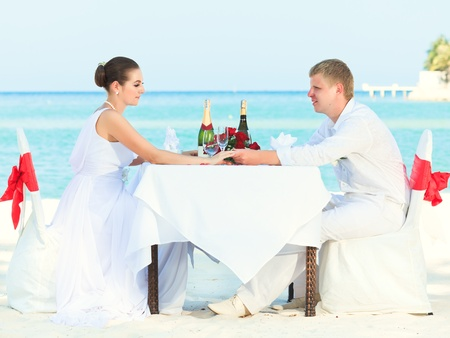 Bride and groom at wedding table on the beach photo