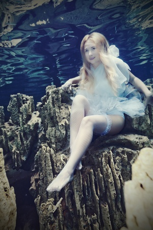 Young beautiful woman in white dress underwater photo