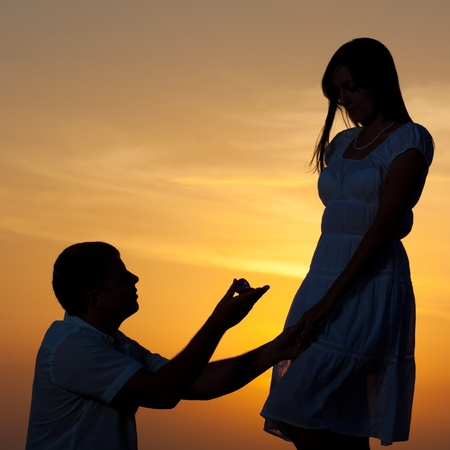 Man proposing to girlfriend and offering engagement ring. Silhouette 免版税图像