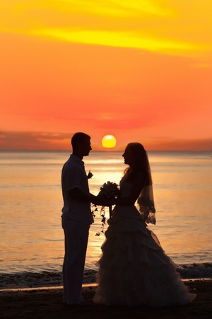 Shape of a bride and groom on the beach at sunrise time Stock Photo - 10452156