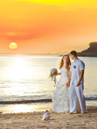 Bride and groom walking on the beach at sunrise photo