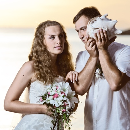 Bride and groom listening seashell music on a beach Stock Photo - 10452154