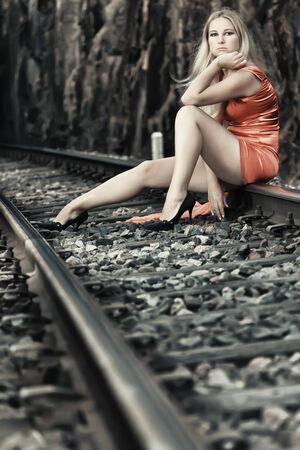 Young beautiful woman sitting on train track photo