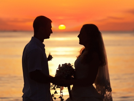 Shape of a bride and groom on the beach at sunrise time photo