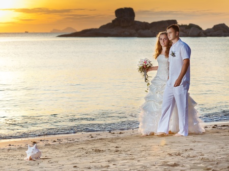 Bride and groom walking on the beach at sunrise