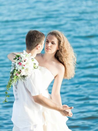 Bride and groom dancing on a rock. photo