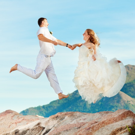 Bride and groom jumping on a rock. Mountain on a background photo