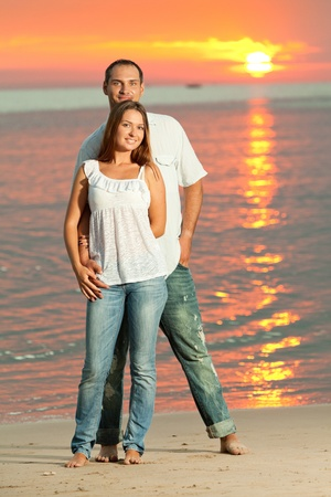 Young couple near the sea at sunrise Stock Photo