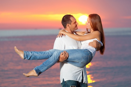 Young couple near the sea at sunrise photo