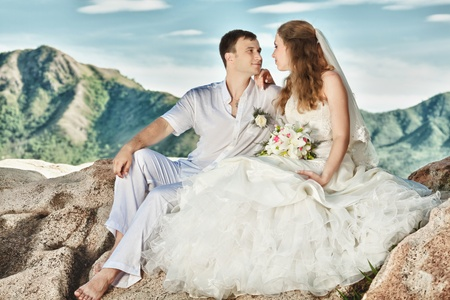 Bride and groom sitting on the rock. Mountain on background photo