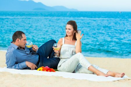Young beautiful couple drinking wine on the beach photo
