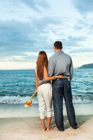 Young beautiful couple staying near the ocean photo