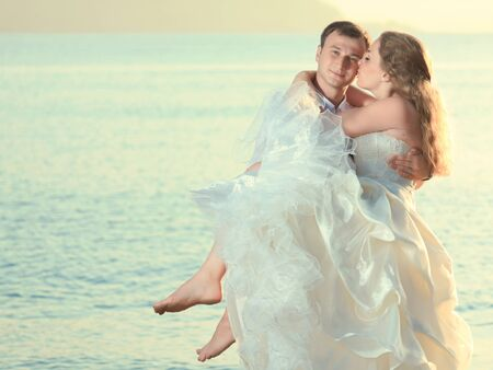 Groom holding up a his bride on the beach photo