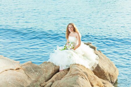 Beautiful bride sitting on a rock in a sea photo
