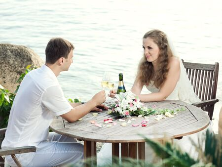 Bride and groom at wedding table near the sea photo