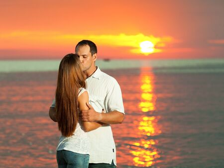Young couple kissing near the sea at sunrise photo