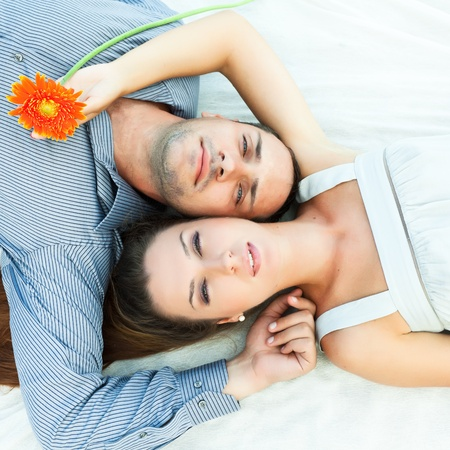 Portrait of young couple lies together outdoor