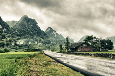 Rural landscape with road; house and mountains. 免版税图像