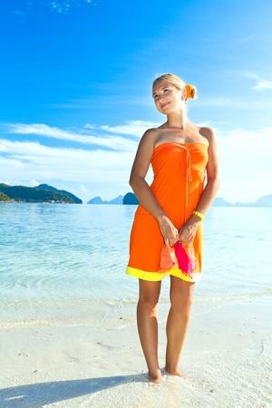 Woman in orange dress on the tropical beach photo