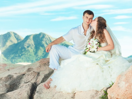 Bride kissing groom on the rock. Mountain on background photo