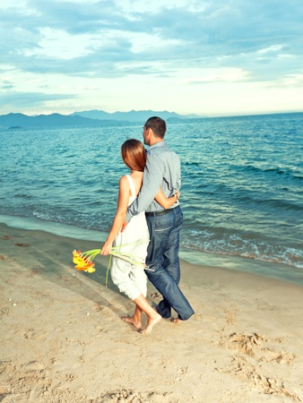 Young beautiful couple walking near the ocean photo