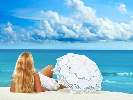 Woman with umbrella on the tropical beach 免版税图像
